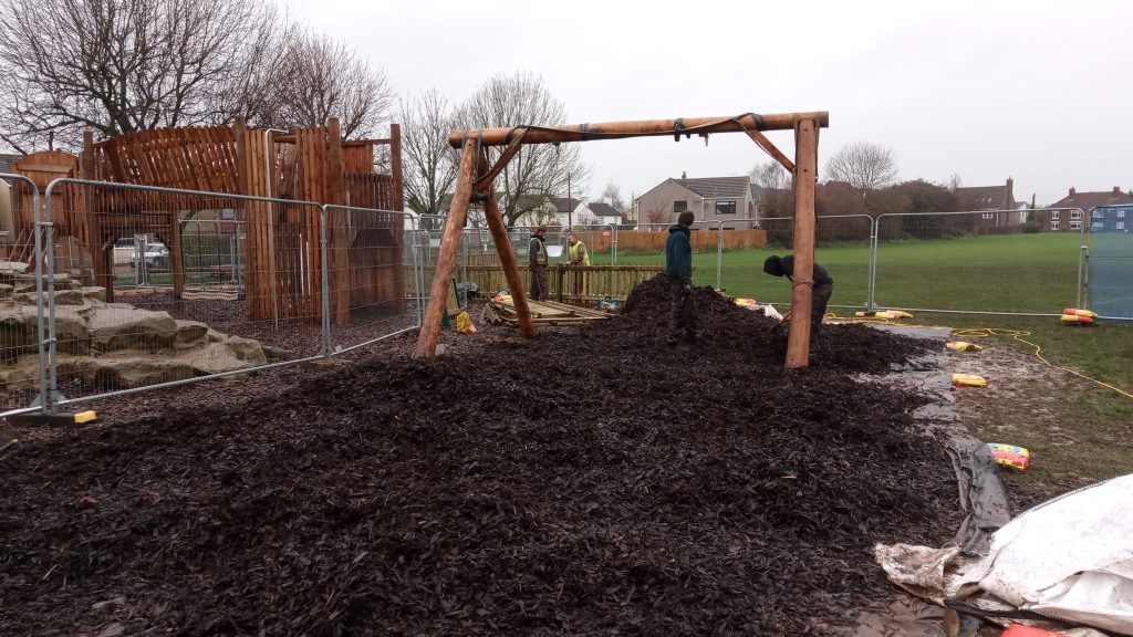 Image of a section of the Beesmoor Road Play Area being redeveloped and adding bark to the ground.