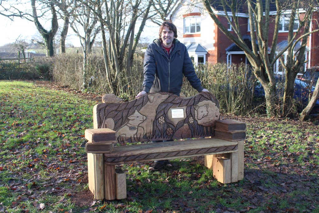 Wood carver with the new bench which has animals carved into it